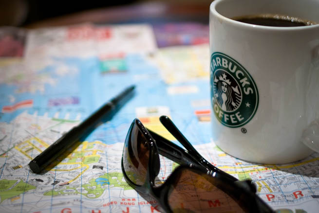 A traveler plans his trip using a map, a pen, and lots of coffee.